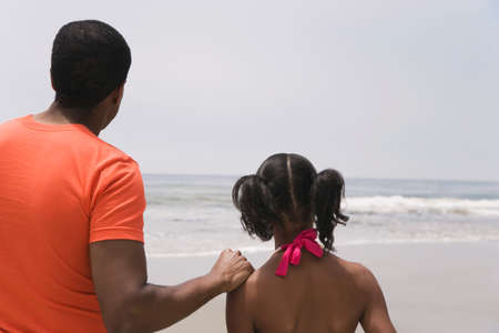 father daughter: African father and daughter looking at ocean