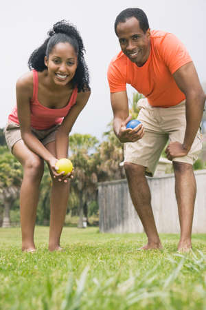 motioning: African couple playing bocci ball