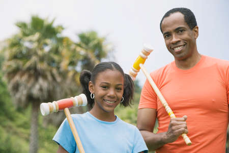 fathering: African father and daughter holding croquet mallets