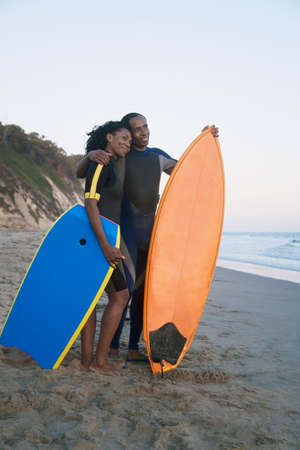 honeymooner: African couple holding surfboard and boogie board