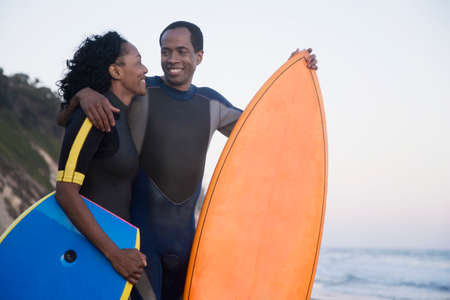 boogie: African couple holding surfboard and boogie board