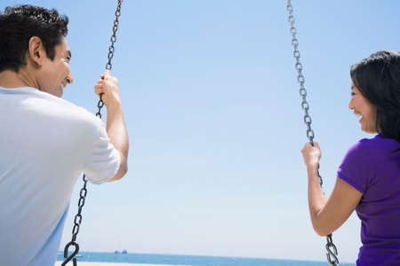 asian adult: Asian couple swinging on swings