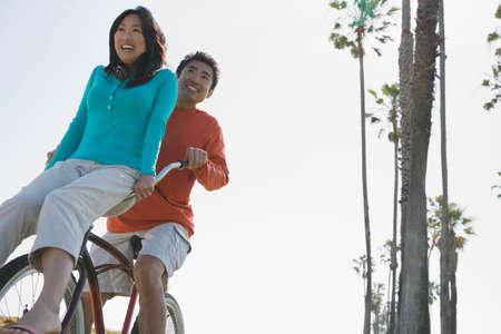 beach cruiser: Asian man riding bicycle with girlfriend on handlebars