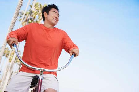 beach cruiser: Asian man riding bicycle
