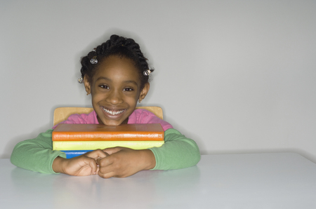 wearying: African girl with stack of school books