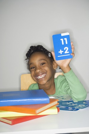 African girl holding addition flash cards