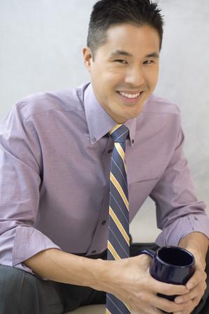 Asian businessman holding coffee mug Banco de Imagens