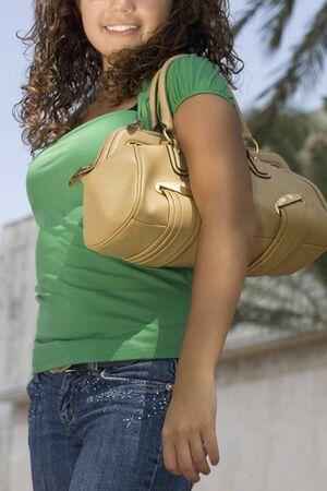 one teenage girl only: Hispanic teenaged girl carrying shoulder bag
