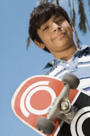 pacific islander ethnicity: Hispanic boy holding skateboard