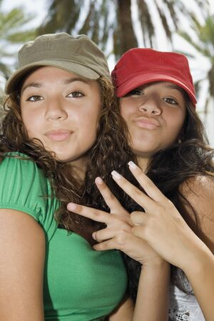 teenaged girls: Hispanic teenaged girls making hand gestures LANG_EVOIMAGES