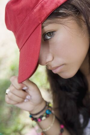 teenaged girl: Hispanic teenaged girl wearing hat