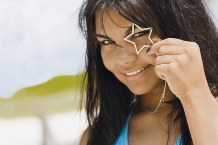 sweats: Hispanic woman holding heart necklace over eye