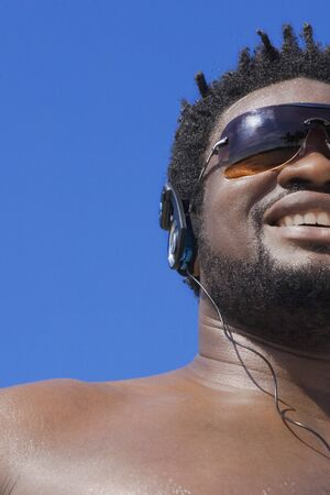 intimidating: African man listening to headphones LANG_EVOIMAGES
