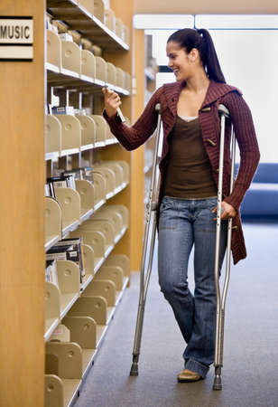 hindering: Hispanic woman in crutches in library