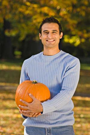 nite: Hispanic man holding pumpkin