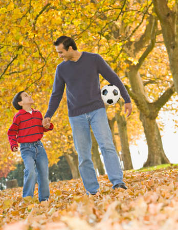 fathering: Hispanic father and son with soccer ball in park