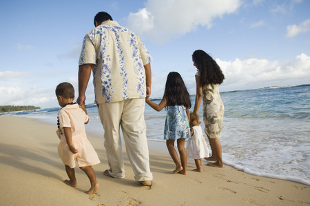 Pacific Islander family walking on beach Stock Photo