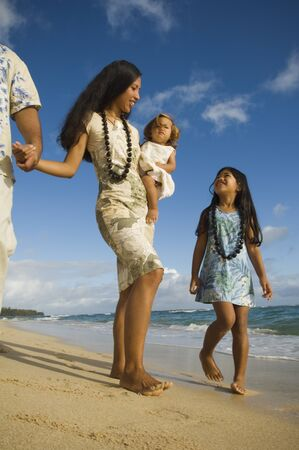 stepping: Pacific Islander family walking on beach