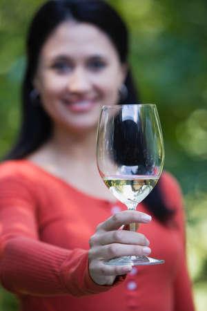 holding up: Hispanic woman holding up wine glass