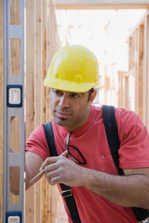 fathering: Mixed Race male construction worker using level
