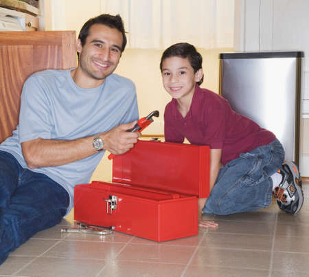 fathering: Hispanic father and son looking in tool box