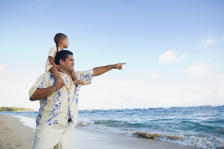 fathering: Pacific Islander father with son on shoulders at beach