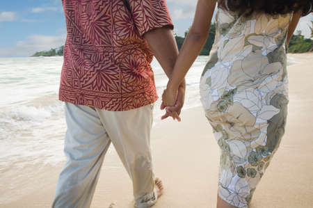 Pacific Islander couple walking on beach