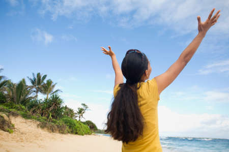 islander: Pacific Islander woman with arms raised at beach LANG_EVOIMAGES