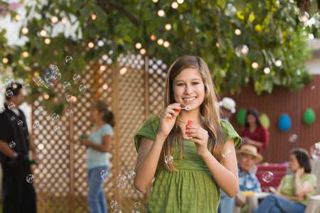 blowing bubbles: Hispanic girl blowing bubbles