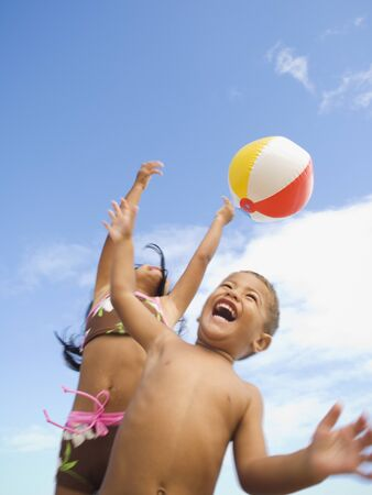 islander: Pacific Islander siblings playing with beach ball LANG_EVOIMAGES