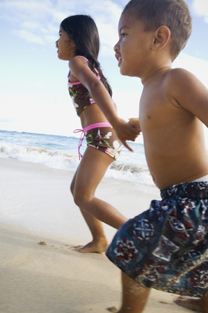 Pacific Islander siblings running on beach Stock Photo
