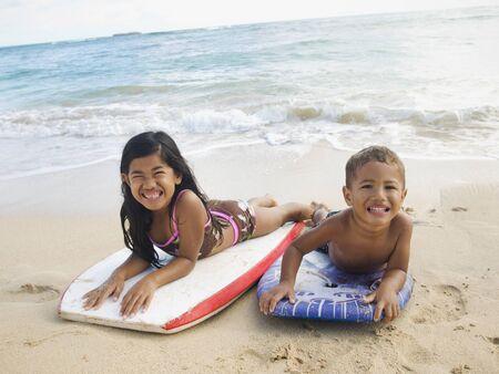 Pacific Islander siblings laying on boogie boards