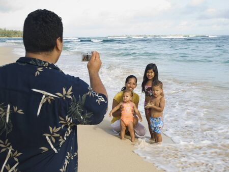 islander: Pacific Islander father taking photograph of family LANG_EVOIMAGES