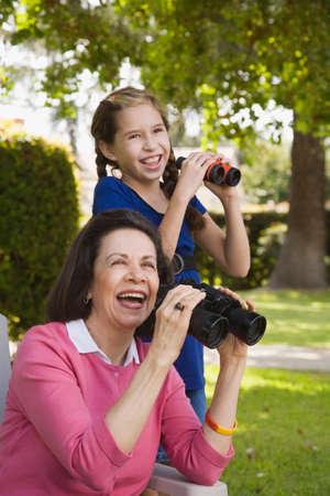 flowergirl: Hispanic grandmother and granddaughter looking through binoculars LANG_EVOIMAGES