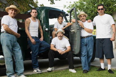 leaning on the truck: Multi-generational Hispanic male family members in front of truck