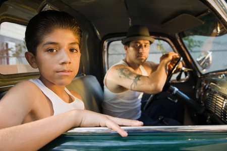 fathering: Hispanic father and son sitting in truck