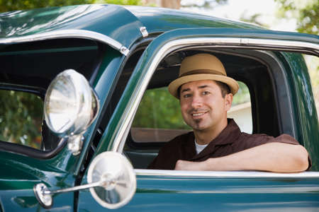 leaning on the truck: Hispanic man sitting in truck