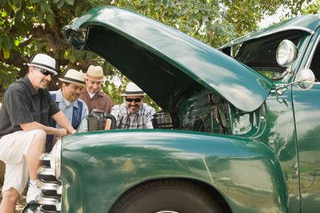 Hispanic men looking under truck hood