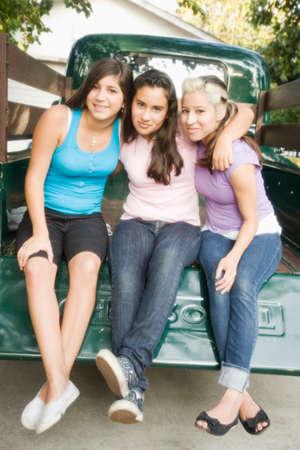 teenaged girls: Hispanic teenaged girls sitting on truck tailgate