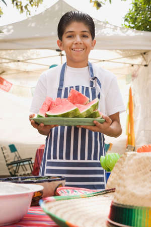 citrus family: Hispanic boy holding plate of watermelon