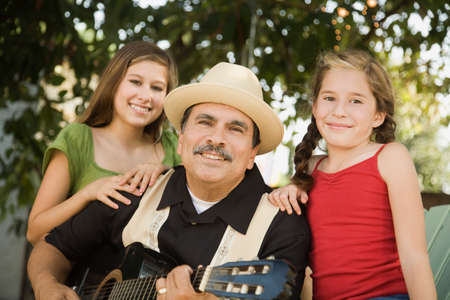 gramma: Hispanic father playing guitar for daughters LANG_EVOIMAGES