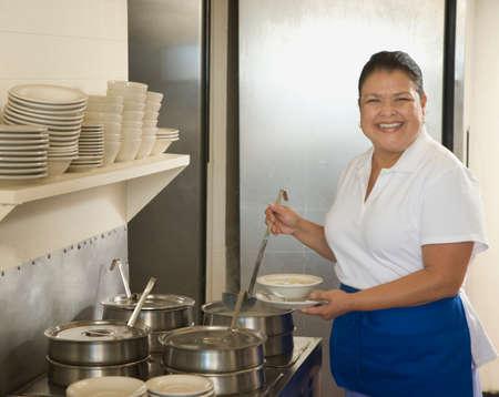 grampa: Hispanic waitress ladling soup LANG_EVOIMAGES