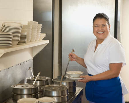 Hispanic waitress ladling soup Stock Photo