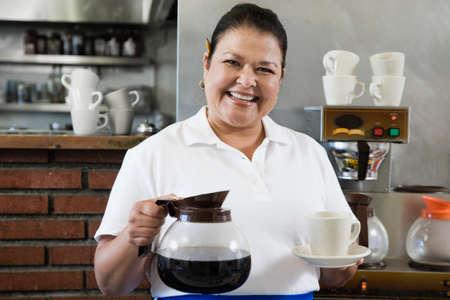 Hispanic waitress holding coffee pot and mug Stock Photo
