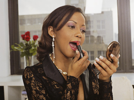 Hispanic woman applying lipstick