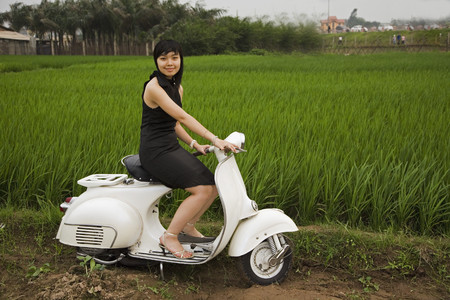 one teenage girl only: Asian woman sitting on motor scooter