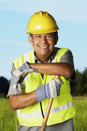 babyboomer: Hispanic man wearing hard hat and reflective vest
