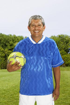 exerting: Hispanic man holding soccer ball