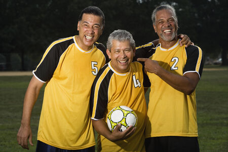 Multi-ethnic men holding soccer ball