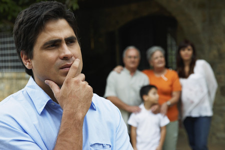 wooing: Hispanic man thinking with family in background